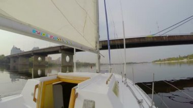 Yacht sailing under river city bridge, cityscape, pollution — Stockvideo