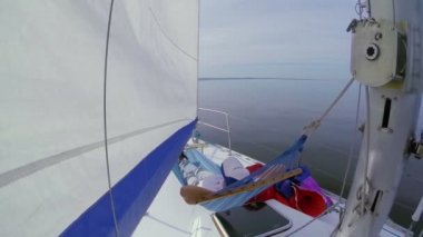 Man lying in hammock on sailboat — Stock Video