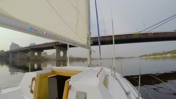 Yacht sailing under city bridge — Vidéo