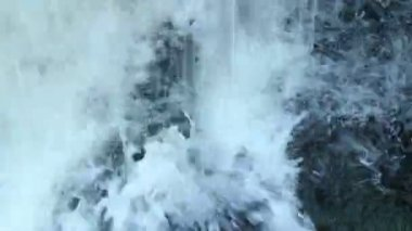 Water flow splashing against rock — Wideo stockowe