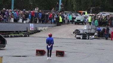 KIEV, UKRAINE - SEPTEMBER 29, 2013 - Bigfoot Crash Show. Petite stunt woman dives under fast-driving car, auto show — Stockvideo