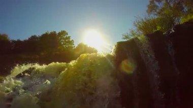 Turbulent waterfall and sun — Stock Video