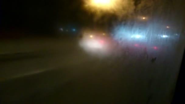 Mirando a través de la ventana mojada en el camino oscuro, tráfico intensivo noche — Vídeo de stock