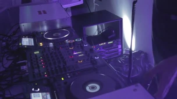 DJ scratching platter at turntable, creating atmosphere at club — Vidéo