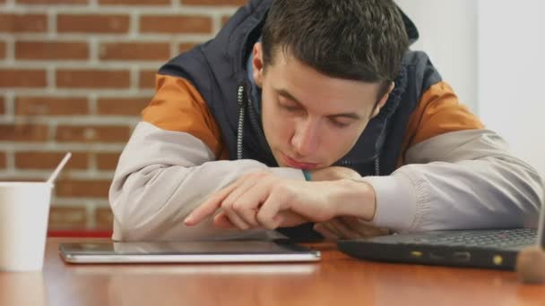 Bored student reading bad news on tablet, alone in cafe — Vidéo
