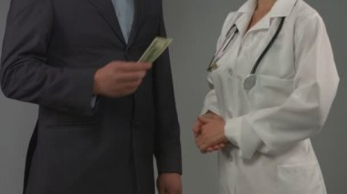 Patient gives money to doctor. Expensive health insurance, bribe — Stok video