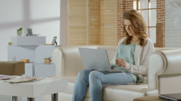 Happy young lady sitting at home, chatting on laptop, smiling — Vidéo