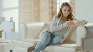 Happy young smiling female chatting with boyfriend on smartphone — Stock Video