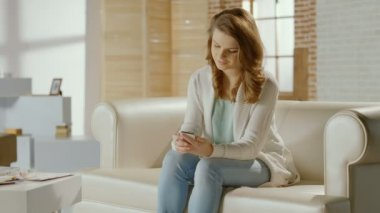 Pretty lady texting, typing message on smartphone in apartment — Stock Video