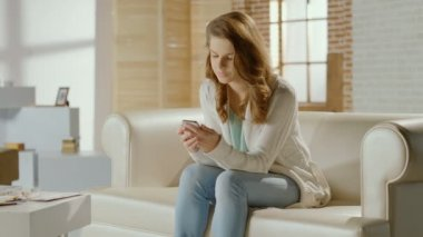 Young female browsing pictures, sending messages on smart phone — Stock Video