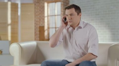 Young man discussing business problems in phone call at home — Wideo stockowe