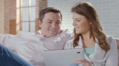 Happy couple sitting on couch with tablet pc. Online shopping — Stockvideo