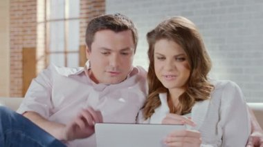 Middle-aged couple talking, laughing, viewing photos on tablet — Stock Video