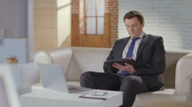 Well-dressed businessman searching scrolling on tablet in office — Stock Video