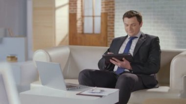 Businessman typing, scrolling pages on tablet, looking at camera — Stock Video