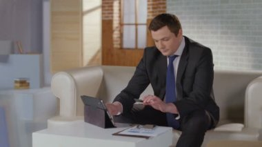Happy businessman enters card number on tablet, looks at camera — Stock Video