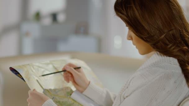 Mujer joven buscando lugar en el mapa, planificación de tour por la ciudad — Vídeo de stock