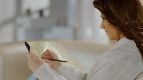 Hermosa mujer joven examinando el mapa, hacer anotaciones con lápiz — Vídeo de stock