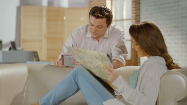 Feliz solo casados planeando viaje de luna de miel, comprobación de mapa — Vídeo de stock