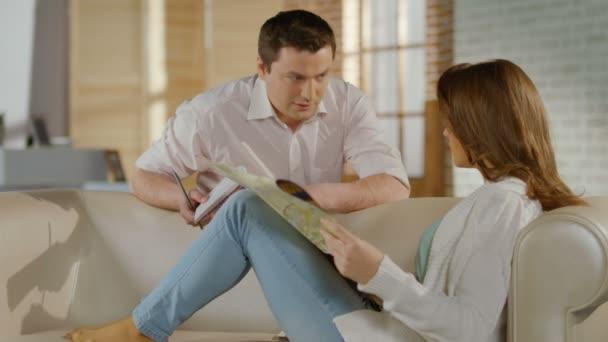 Joven, mujer, comprobación de mapa, hablando, planeando vacaciones familiares — Vídeo de stock