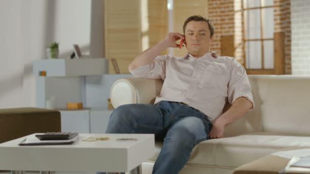 Joven sentado en el sofá en casa, tener conversación telefónica — Vídeo de stock