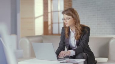 Pretty business lady in glasses typing on laptop, office worker — Stock Video
