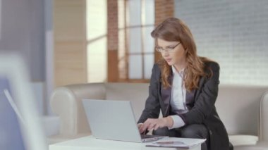 Beautiful woman office employee typing on laptop, smiling at cam — Stock Video