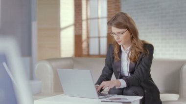 Lady in business suit, glasses works on laptop, smiles at camera — Stock Video