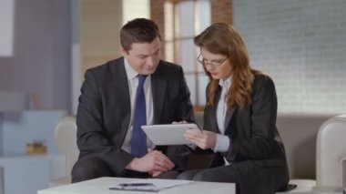 Real estate agent showing photos on tablet to businessman client — Stock Video