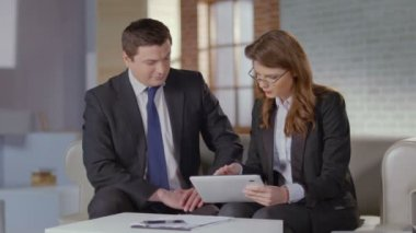 Sales manager shows charts to business client on tablet, slow-mo — Stock Video