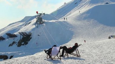 Two relaxed men sitting in chairs, observing snowy skiing run — Vidéo