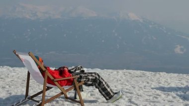 Snowboarder having rest in chair with gadget on top of mountain — 图库视频影像