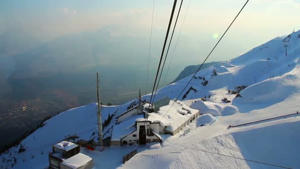 View from cableway cabin lifting skiers to snowy mountain pick — Vídeo de stock
