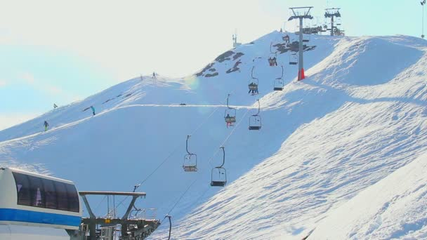 Cable way moving tourists, skiers up down snowy mountain in Alps — Vídeo de stock