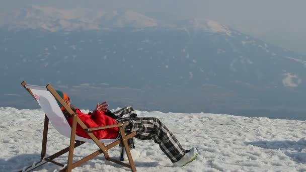 Snowboarder having rest in chair with gadget on top of mountain — Vídeo de stock