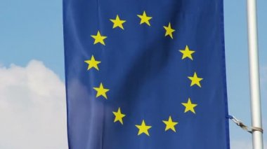 Flag of European Union waving in wind, blue sky background — Stock Video