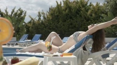 Attractive young female suntanning near swimming pool, vacation — Stockvideo