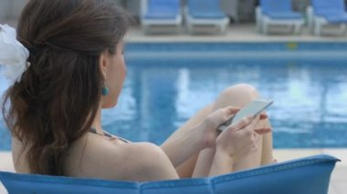 Young woman dialing number, calling, talking on phone near pool — Stock Video