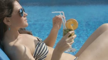 Hot chick drinking cocktail near swimming pool, smiling, teasing — Stock Video