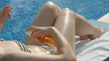 Beautiful model spraying tanning oil on body, massaging her skin — Stock Video