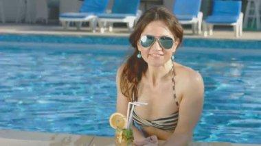 Beautiful girl bikini relaxes in pool, enjoys cocktail, vacation — Stock Video