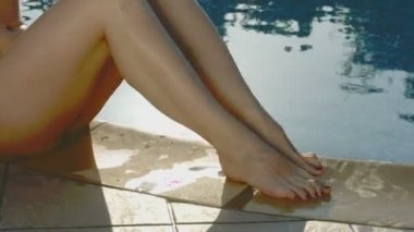 Attractive female legs playfully splashing water out of the pool — Stock Video