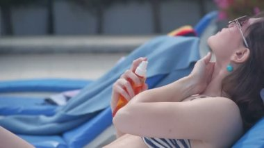 Sexy girl gently putting sunscreen on hot body, enjoying rest — Stock Video