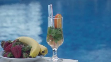 Cocktail and fruit near swimming pool, blue water background — Stock Video
