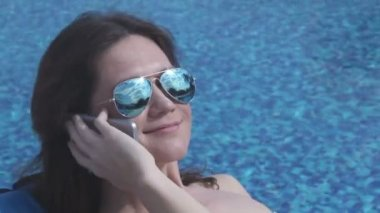 Pretty lady talking on phone near pool, flirting, smile on face — Stock Video