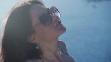 Seductive woman in sunglasses tanning in sunlight at resort — Stock Video