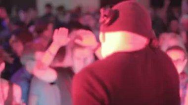 Male disk jockey playing set at nightclub, crowd enjoying music — Stock Video
