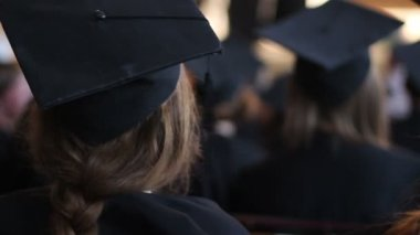 Young female in academic dress at diploma award ceremony, listening to lecture — Stock Video