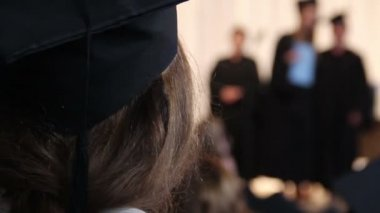 Girl in academic cap looking at students receiving diplomas, college graduation — Stock Video
