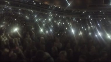 Stadium full of people waving hands, phone screens shine in darkness, love song — Stock Video